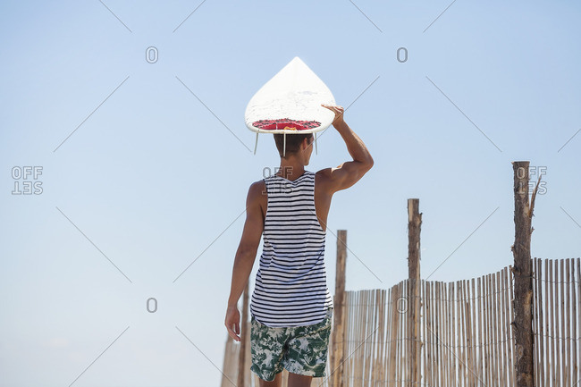Man carrying surfboard on head while standing at beach