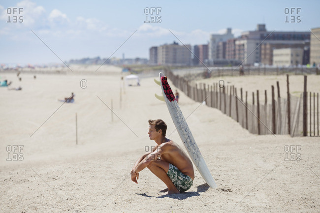 Side view of man with surfboard crouching at beach on sunny day