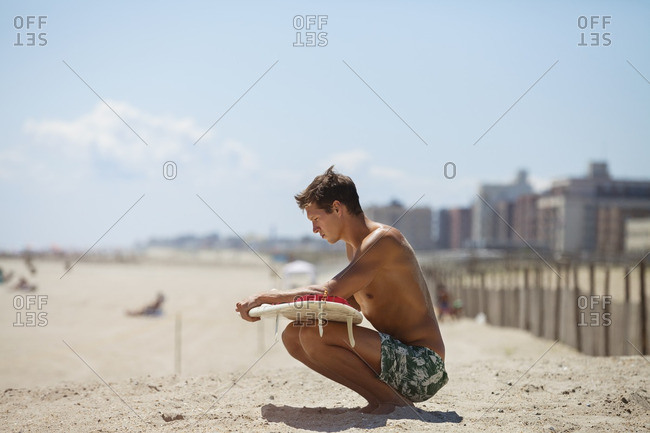 Man looking at surfboard while crouching on sand against sky