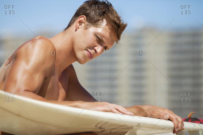 Man examining surfboard at beach on sunny day
