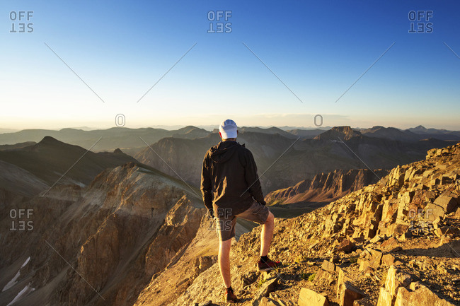 Rear view of man looking at mountains while standing on rock against clear sky