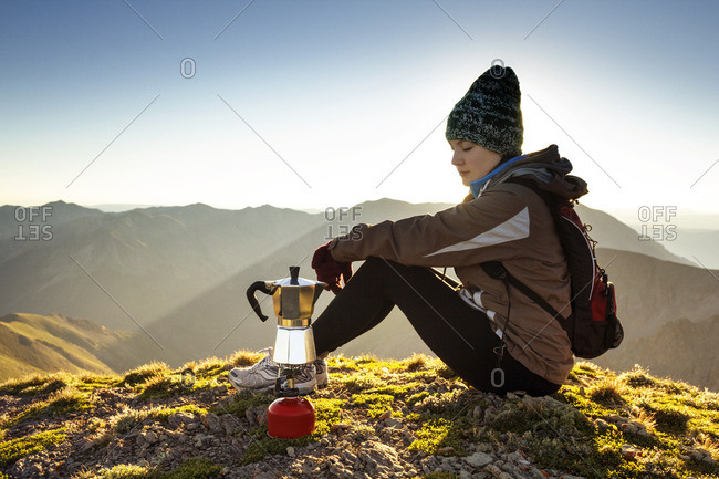 Female backpacker making coffee while sitting on mountain against clear sky