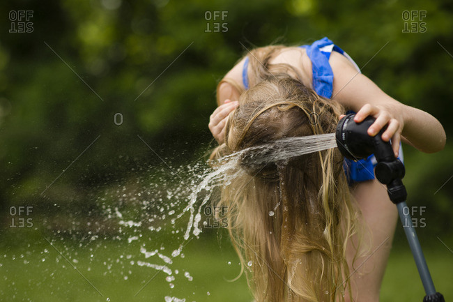 Girl pouring water on hair with hose at backyard