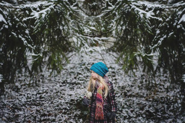Girl with stuffed toy standing at backyard during winter