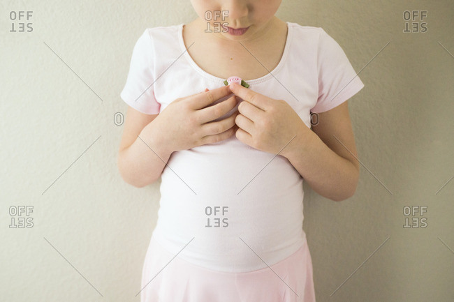 Girl looking at dress while standing against wall at home