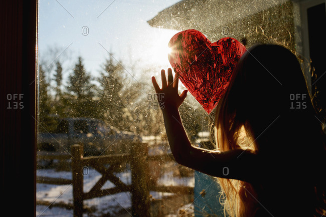 Girl drawing heart shape on window at home