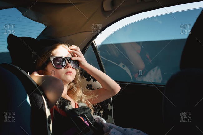 Girl in sunglasses sitting in car