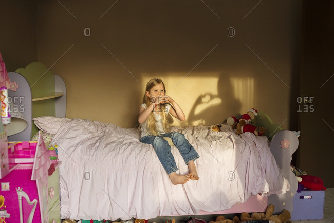 Girl making heart shape with hands while sitting on bed at home