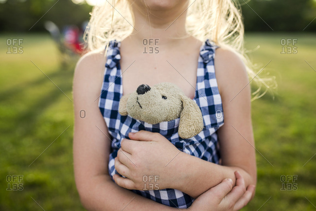 Midsection of girl holding stuffed toy in dress on field at backyard