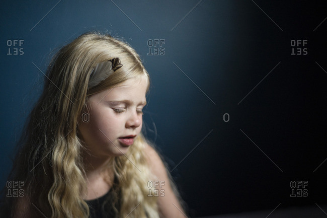 Girl with feather in hair sitting at home