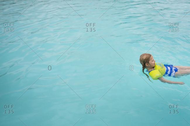 Girl floating in swimming pool