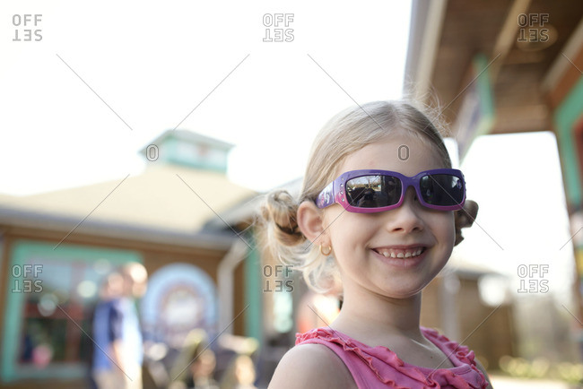 Happy girl in sunglasses standing outdoors