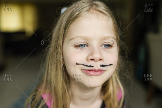 Girl with mustache face paint at home