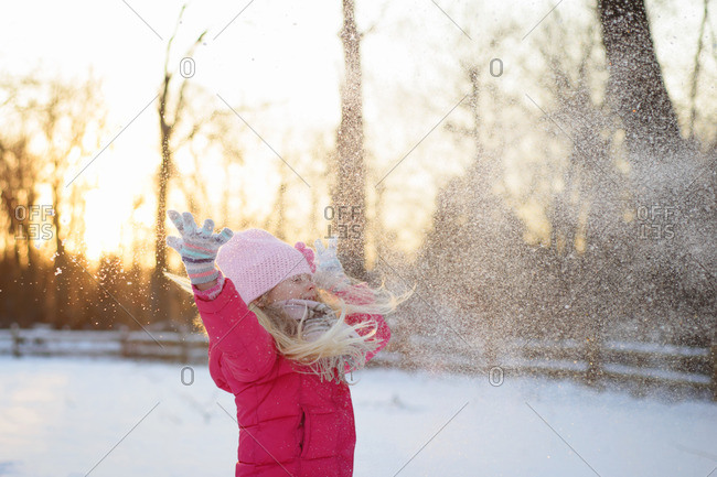 Girl in warm clothing throwing snow while standing against sky