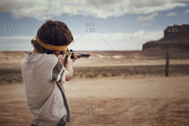 Boy aiming rifle while standing on field against sky