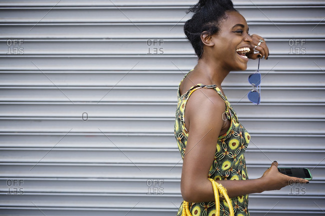 Woman laughing while standing against shutter