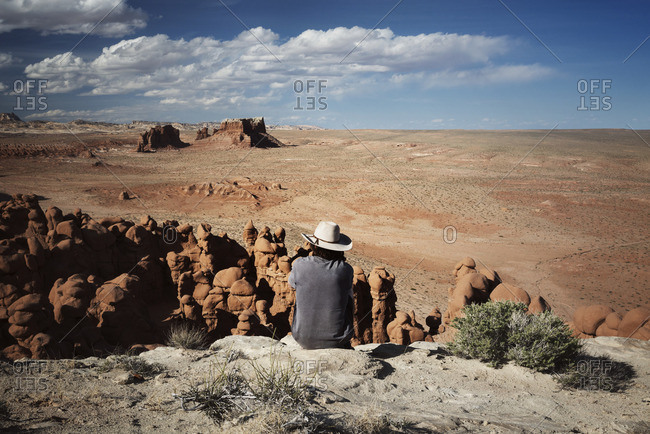 Rear view of man looking at view while siting on rock formation against sky