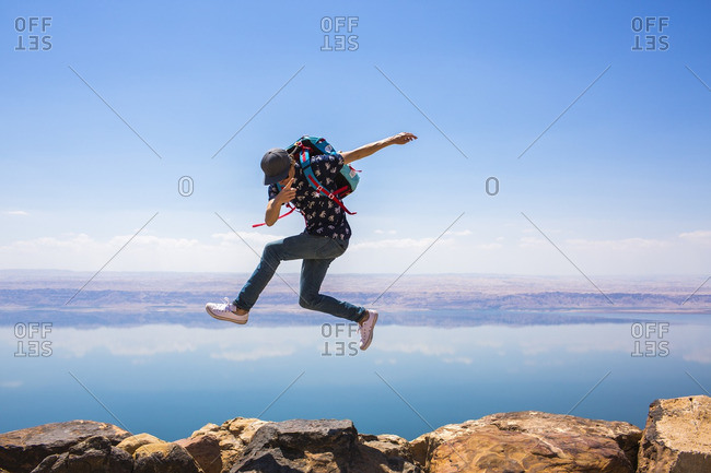 Happy woman jumping on mountain against sea
