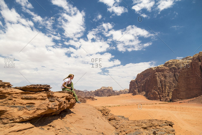 Woman sitting on rock against sky on sunny day