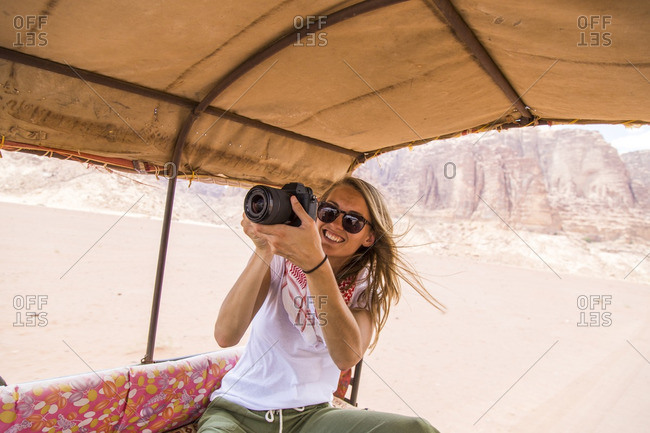 Happy woman in sunglasses photographing while traveling in vehicle