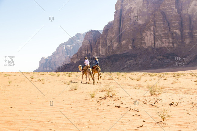 Friends riding on camel in desert against clear sky