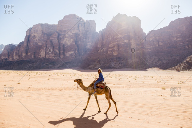 Woman riding on camel in desert