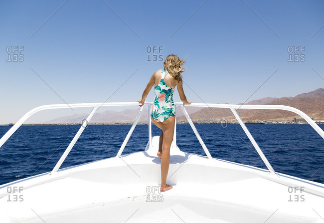 Rear view of woman standing on boat