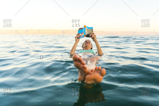 Woman reading book while floating in sea