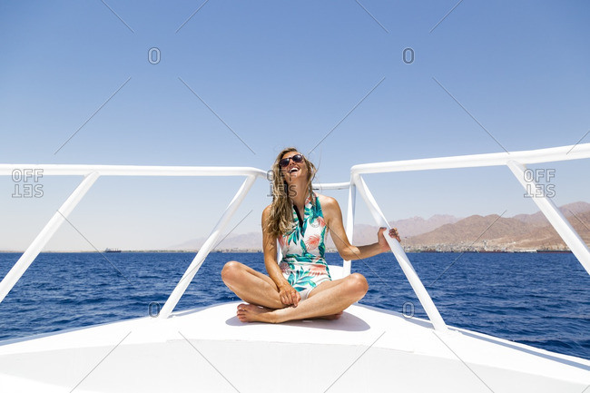 Happy woman sitting on boat against clear sky