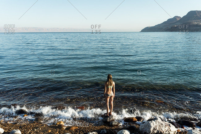 Rear view of woman looking at sea while standing on rock