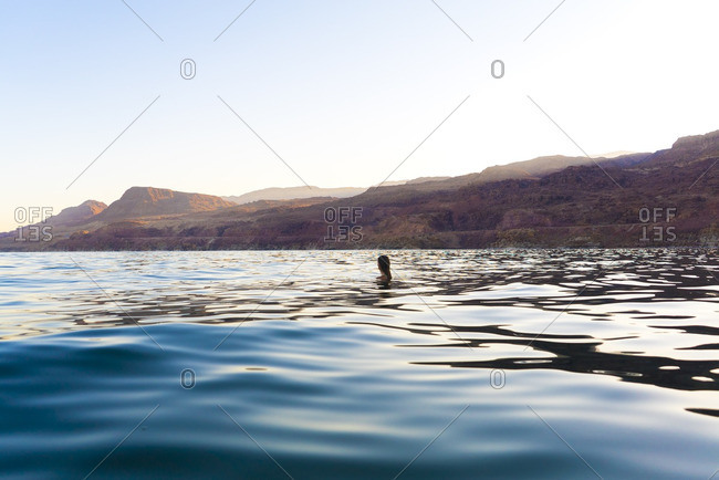 Woman swimming in sea against clear sky during sunset
