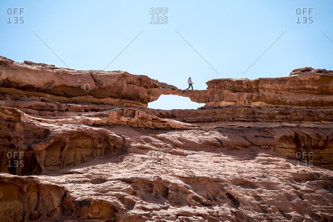 Woman walking on rock formation against clear sky