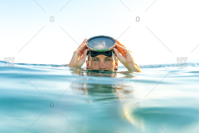 Portrait of woman swimming in sea against clear sky