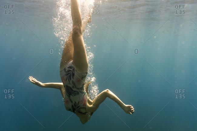 Woman swimming upside down in sea