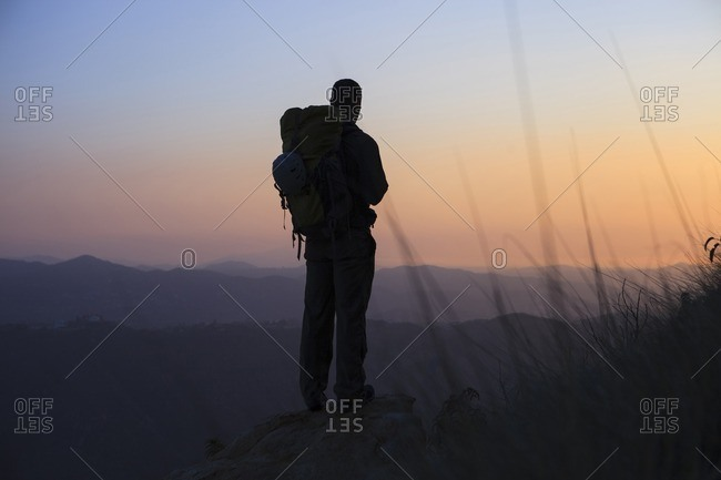 Silhouette man standing on rock and looking at view during sunset