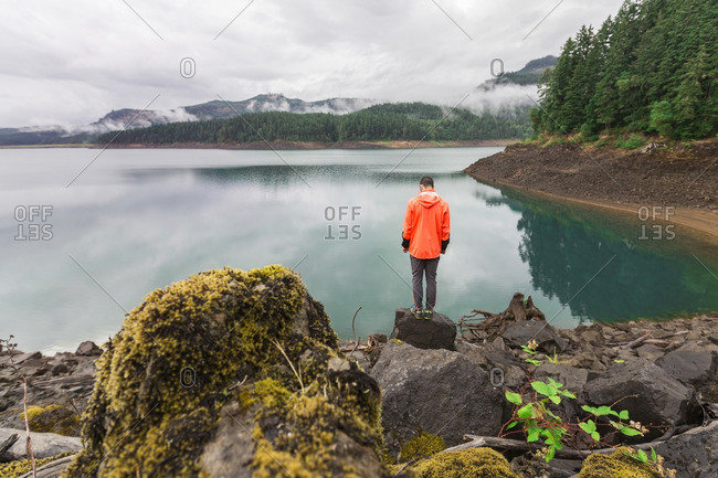 Rear view of man standing on rock by lake against cloudy sky