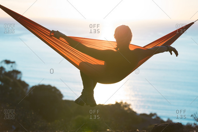 Woman relaxing on hammock on sunny day