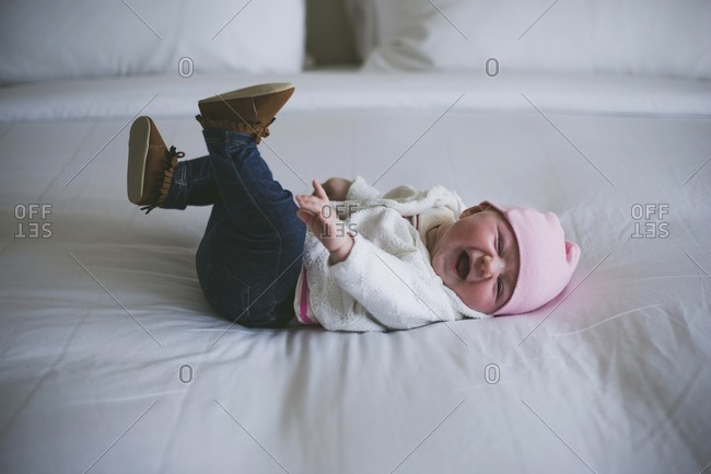 Cheerful baby laughing while lying on bed at home