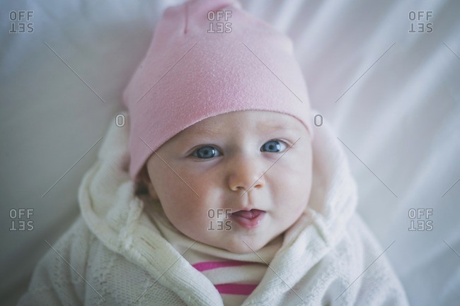 Portrait of baby in warm clothing lying on bed at home