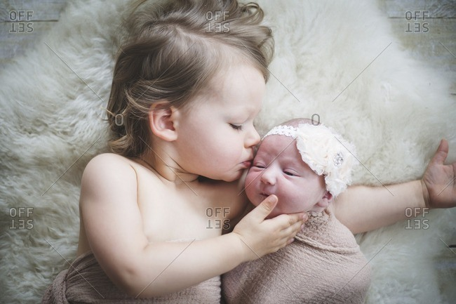 Girl kissing baby sister lying on rug at home