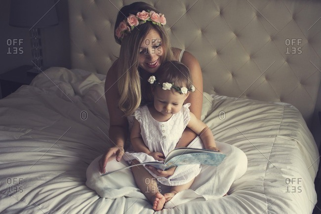 Happy mother reading story book for daughter while sitting on bed at home