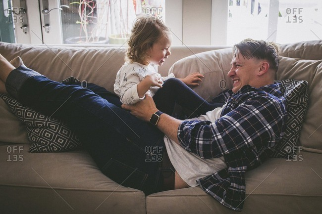 Father playing with girl on sofa at home