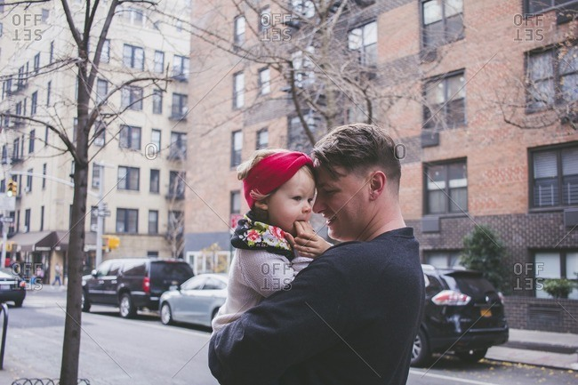 Happy father carrying daughter while standing on footpath