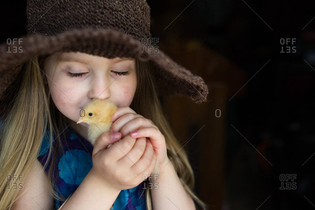 Girl snuggling a chick