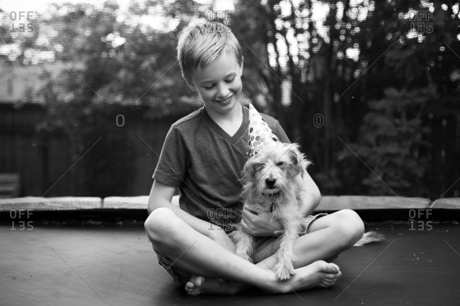 Boy holding dog with party hat