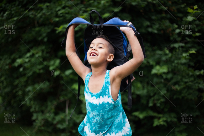 Girl holding up backpack outside