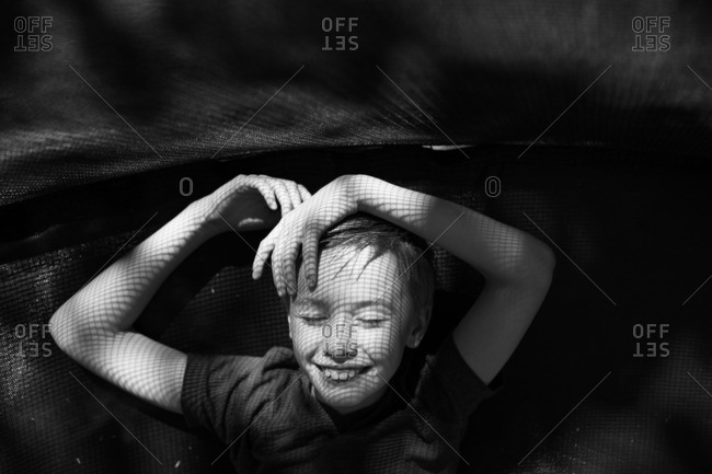 Smiling boy lying on a trampoline