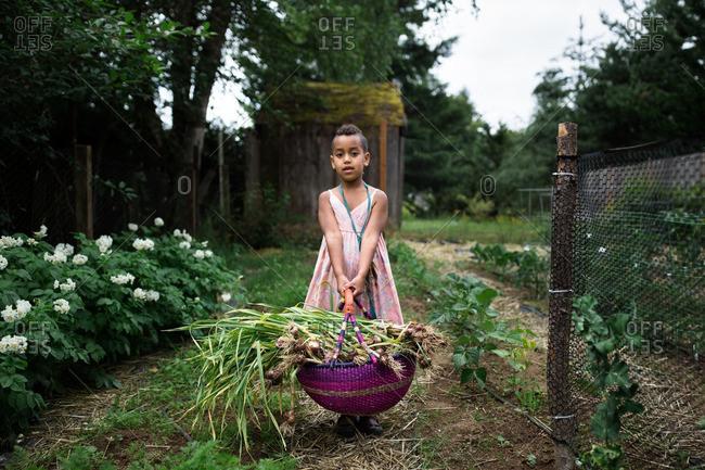 Girl holding vegetable garden crop