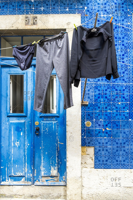 Lisbon, Portugal - April 16, 2014: Laundry on rope against vibrant tiled wall and painted blue doors of house in Alfama District of Lisbon, Portugal