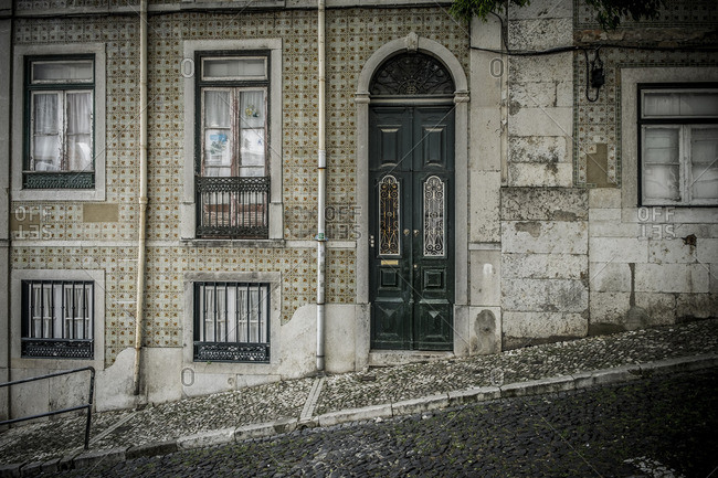 Lisbon, Portugal - April 16, 2014: Grungy house on hilly paved street in Alfama District of Lisbon, Portugal